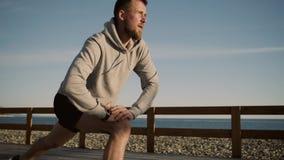 El individuo hermoso está estirando los músculos de las piernas que hacen estocadas cerca del mar almacen de video
