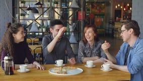 El individuo hermoso feliz está contando historia divertida a sus amigos mientras que cena en café mientras que sus compañeros es metrajes