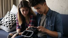 El individuo hermoso joven del mulato inserta un cierto detalle en las VR-auriculares Su novia caucásica se está sentando al lado almacen de video