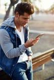 El individuo hermoso joven muy atractivo con un corte de pelo elegante y una chaqueta dzhisovoy lee el mensaje en el teléfono móv Imagen de archivo