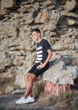 El individuo hermoso se sienta en las rocas Fotografía de archivo