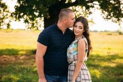 El individuo hermoso y una muchacha atractiva se abrazan cerca de un árbol verde grande Historia de amor foto de archivo