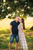 El individuo hermoso y una muchacha atractiva se abrazan cerca de un árbol verde grande Historia de amor fotos de archivo
