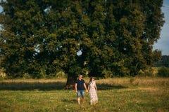 El individuo hermoso y una muchacha atractiva se abrazan cerca de un árbol verde grande Historia de amor imagen de archivo libre de regalías