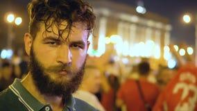 El individuo joven adulto del inconformista mira la cámara severo contra huelga en una ciudad de la noche metrajes
