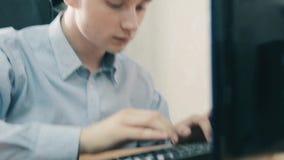 El individuo joven con confianza y trabaja rápidamente en el ordenador metrajes