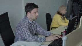 El individuo joven con los auriculares trabaja en el ordenador en la oficina metrajes