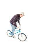 El individuo joven con una bicicleta aislada en un blanco Fotografía de archivo