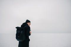 El individuo joven del inconformista se vistió en negro en el invierno en el lago congelado con una taza de café a disposición Imágenes de archivo libres de regalías