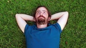 El individuo joven duerme en hierba almacen de video