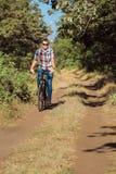 El individuo joven en el bosque con la bicicleta Fotografía de archivo libre de regalías