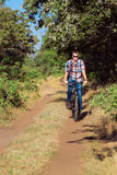 El individuo joven en el bosque con la bicicleta Foto de archivo
