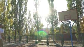 El individuo joven en el patio lanza la bola almacen de video