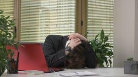El individuo joven en un traje se está sentando en la oficina, trabajando en un ordenador portátil, cansado, el caer dormido, agu almacen de metraje de vídeo