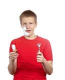 El individuo joven en una camiseta roja con la maquinilla de afeitar y un pequeño cepillo en manos Fotos de archivo libres de regalías