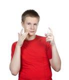 El individuo joven en una camiseta roja para poner la crema cosmética en una cara. Retrato en un fondo blanco Fotos de archivo