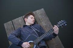 El individuo joven en una capilla toca la guitarra en el puente por la tarde contra el contexto de una puesta del sol en el río Fotografía de archivo libre de regalías