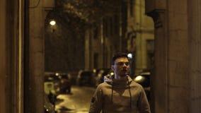 El individuo joven en vidrios corre en backstreet y sonríe en la noche almacen de video