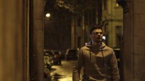 El individuo joven en vidrios corre en la calzada y sonríe en la noche almacen de video