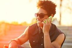 El individuo joven está hablando en el teléfono en el fondo de la puesta del sol Imagenes de archivo