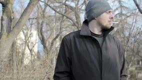 El individuo joven fuma en un parque almacen de metraje de vídeo