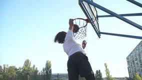 El individuo joven lanza un baloncesto en la red del baloncesto almacen de metraje de vídeo
