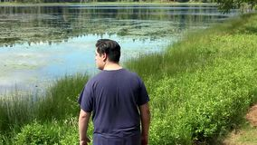 El individuo joven mira el lago metrajes
