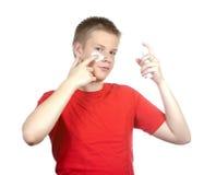 El individuo joven para poner la crema cosmética en una cara. Retrato en un fondo blanco Fotos de archivo libres de regalías