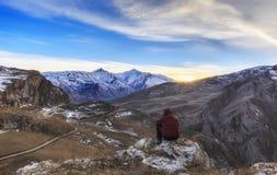 El individuo joven pasa por alto los alrededores montañosos del pueblo Imagenes de archivo