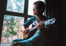 El individuo joven plaing en la guitarra y se sienta cerca de la ventana Imágenes de archivo libres de regalías