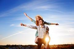 El individuo joven que lleva a cuestas a la novia alegre le gusta el aeroplano en el fondo del cielo fotografía de archivo libre de regalías