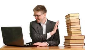 El individuo joven que trabaja en una computadora portátil y encoge apagado los libros de papel Fotografía de archivo