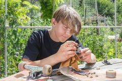 El individuo joven repara las ruedas en un monopatín en una parada de madera en el jardín fotos de archivo