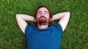 El individuo joven se acuesta en hierba almacen de metraje de vídeo