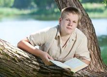 El individuo joven se prepara para las lecciones, examen en parque de la primavera cerca del lago Fotografía de archivo libre de regalías