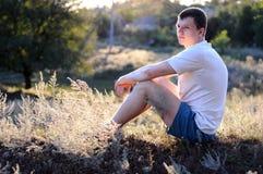 El individuo joven se sienta en Imagenes de archivo