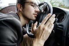 El individuo joven soñoliento inclina su cabeza en el volante Sus manos están en el volante Concepto de la seguridad en carretera foto de archivo libre de regalías