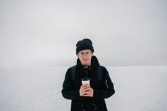 El individuo joven sonriente del inconformista se vistió en lentes de sol negros e invierno en el lago nevado y una taza de café  Foto de archivo