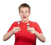 El individuo joven sorprendido en una camiseta roja con la maquinilla de afeitar y un pequeño cepillo en manos Fotos de archivo