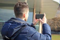 El individuo joven toma imágenes en el teléfono en el parque fotos de archivo