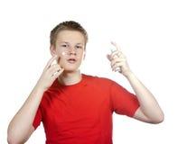 El individuo joven utiliza una crema de cara Imagen de archivo libre de regalías