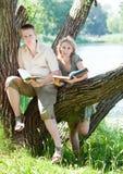 El individuo joven y la muchacha leyeron los libros en el lago Foto de archivo