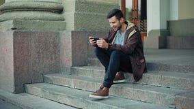 El individuo juega a un juego online en los pasos en la ciudad Ganador satisfecho almacen de video