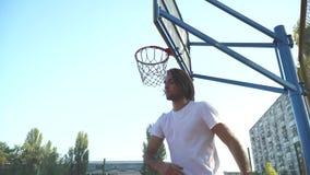 El individuo lanza un baloncesto en la red del baloncesto almacen de video