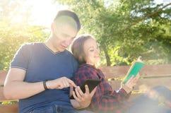 El individuo lee el libro en la tableta al lado de la muchacha que se sienta lee el libro en día soleado del verano en parque fotografía de archivo