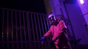 El individuo lindo que lleva la chaqueta y las gafas de sol rojas enérgico canta en la noche almacen de metraje de vídeo