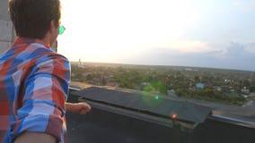 El individuo lleva a cabo la mano de su novio y corre para afilar del tejado para admirar la visión Sígame tiro del hombre joven  almacen de video