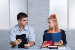 El individuo lleva a cabo un eBook y los controles de una muchacha un libro ordinario, la gente joven miran uno a con caridad Imagenes de archivo