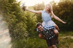 El individuo lleva a su novia en el suyo detrás en verano al aire libre foto de archivo libre de regalías