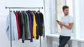 El individuo marca en el mensaje de teléfono, él es frío, él quiere llevar un suéter almacen de video